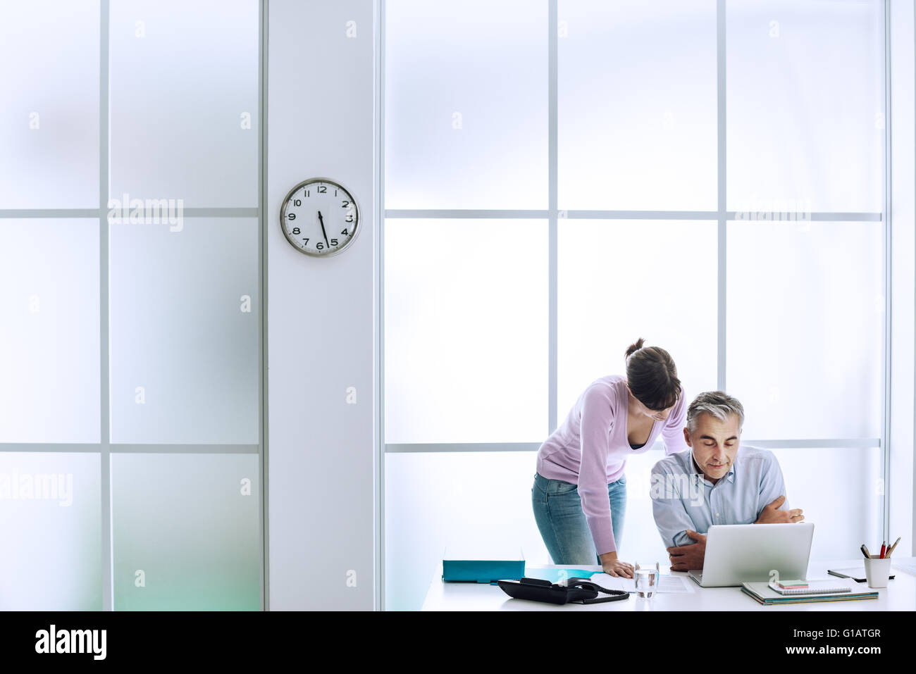 Executive working at office desk with his assistant, they are using a laptop and connecting to internet - Stock Image