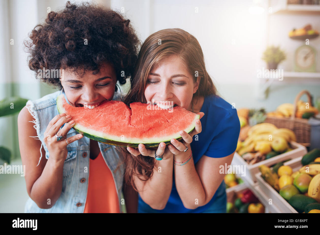 Two young woman eating watermelon and having fun. Mixed race female friends together eating a watermelon slice. - Stock Image