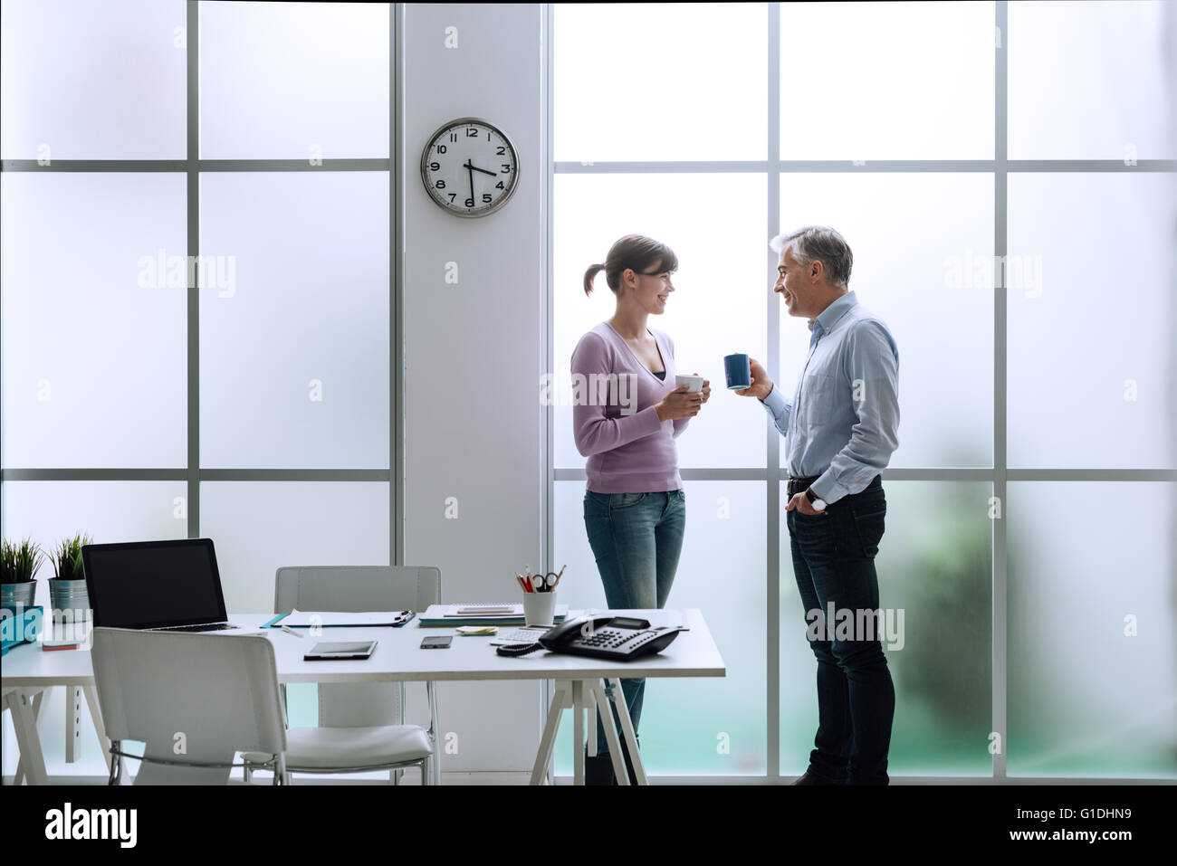 Cheerful office workers in the office, relaxing, having a coffee break and chatting together, they are standing - Stock Image