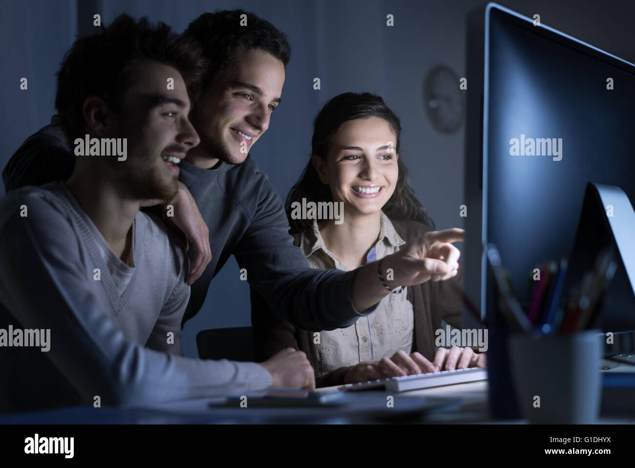 Smiling students connecting to internet with a computer, they are networking and browsing websites, one man is pointing - Stock Image