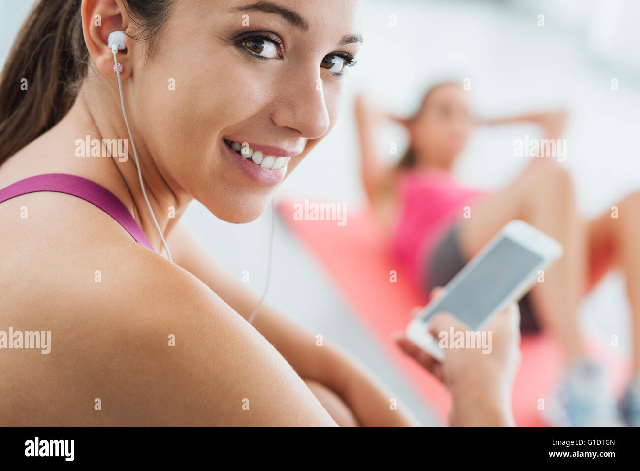 Young smiling woman at the gym having a break and listening to music using a smart phone and earphones, fitness - Stock Image