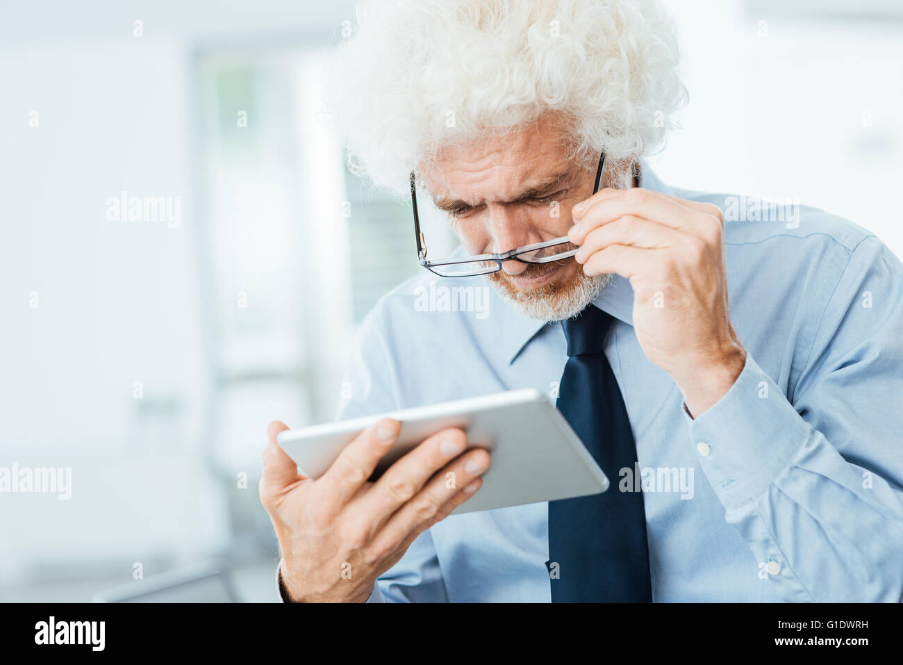 Businessman having eyesight problems, he is using a tablet and adjusting his glasses, office interior on background - Stock Image