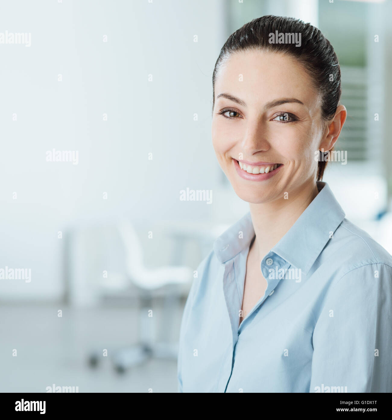 Beautiful young smiling business woman smiling and looking at camera, office interior on background - Stock Image