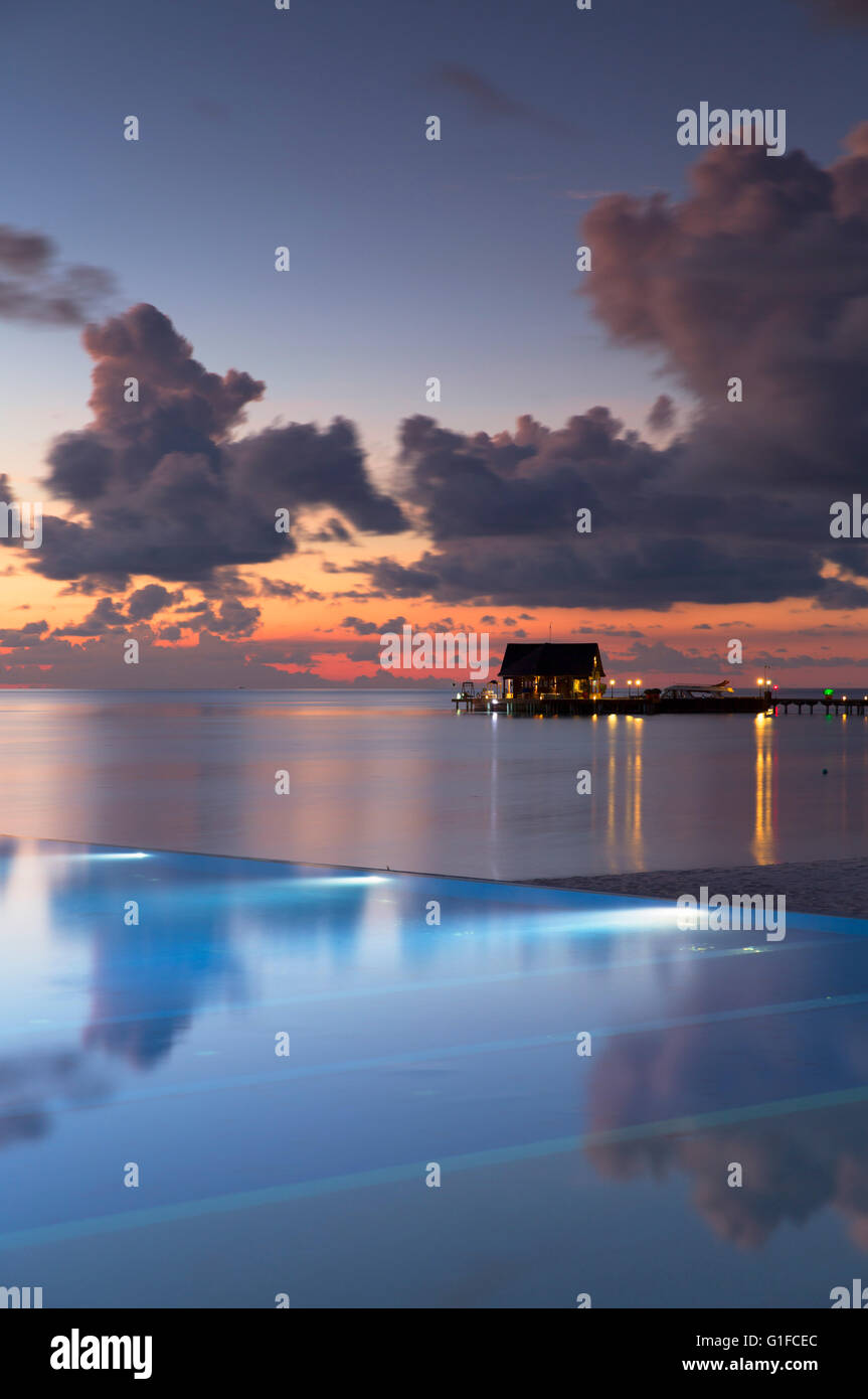 Infinity pool at Olhuveli Beach and Spa Resort at sunset, South Male Atoll, Kaafu Atoll, Maldives - Stock Image