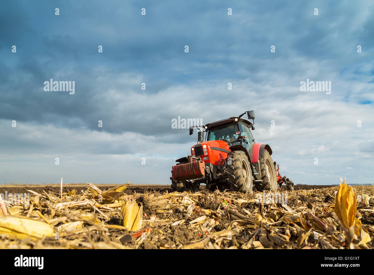 Farmer plowing with red tractor - Stock Image