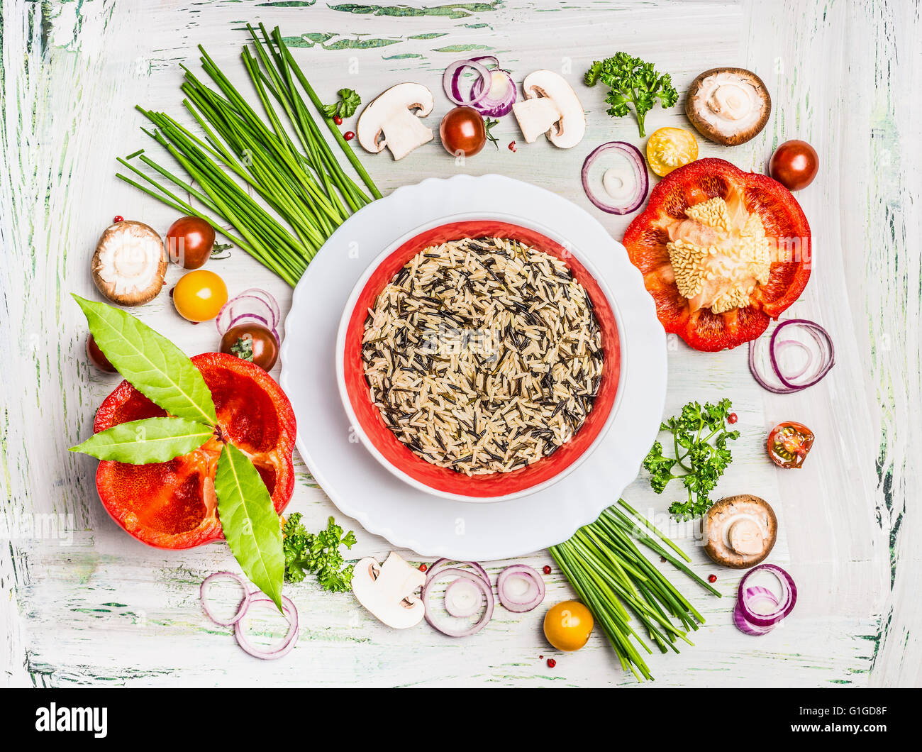 Wild rice dish and various vegetables and seasoning ingredients for tasty vegetarian cooking on light  rustic wooden - Stock Image