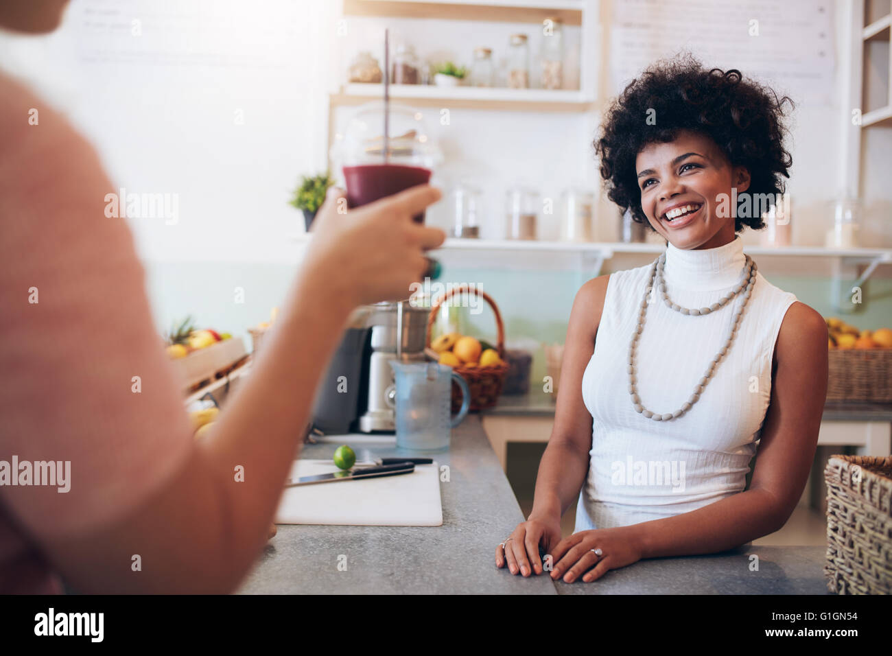 Juice bar owner with female customer holding a glass of fresh juice. African woman standing behind the counter and - Stock Image