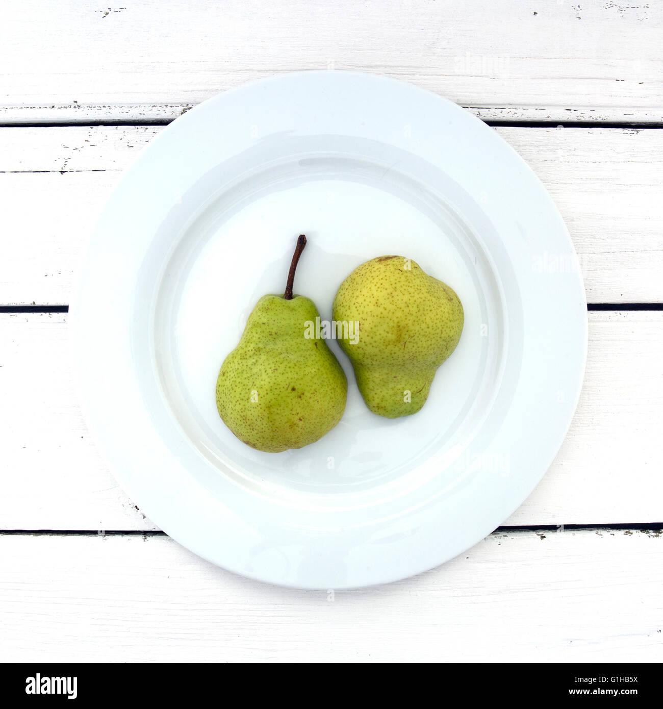 Two Pear Half's on a white plate over a retro white wooden background - Stock Image