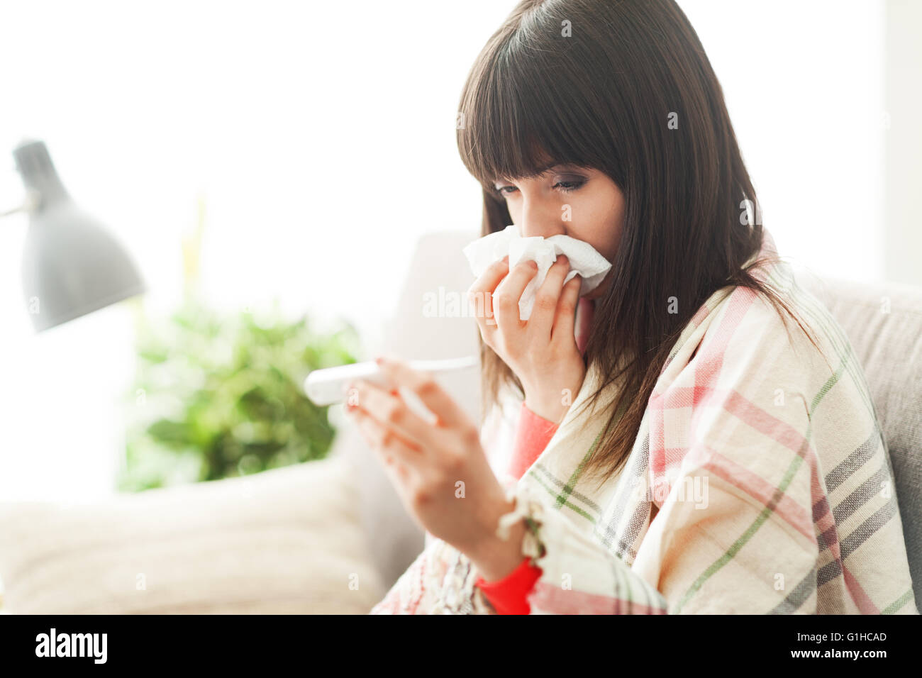 Young sick woman with cold and flu, she is blowing her nose and measuring her body temperature - Stock Image