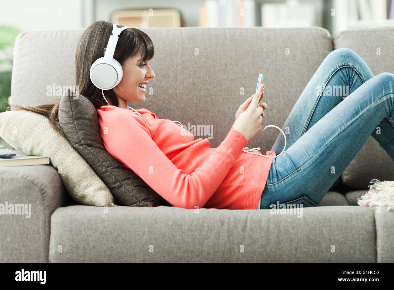 Attractive young woman on the sofa at home, she is playing music with her smarphone and wearing headphones, leisure - Stock Image