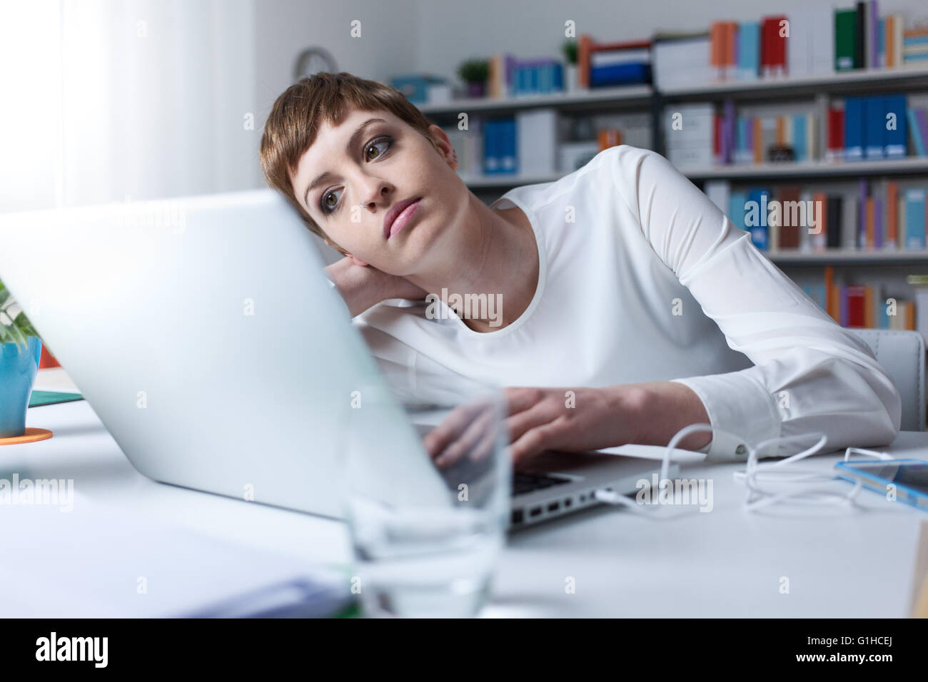 Tired woman in the office leaning on her hand an using a laptop - Stock Image