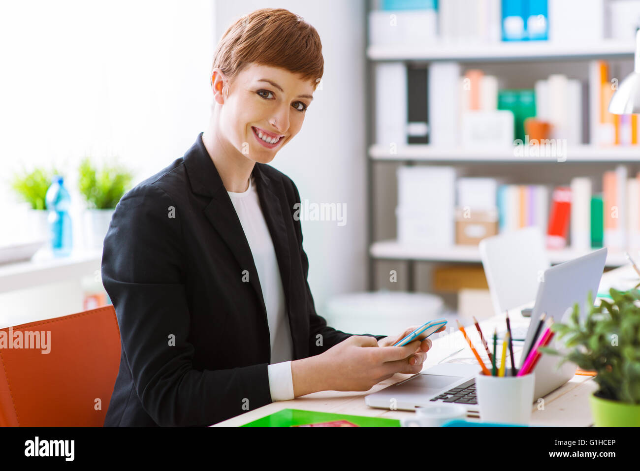 Successful confident businesswoman in her office using a smart phone, she is texting and using a mobile app - Stock Image