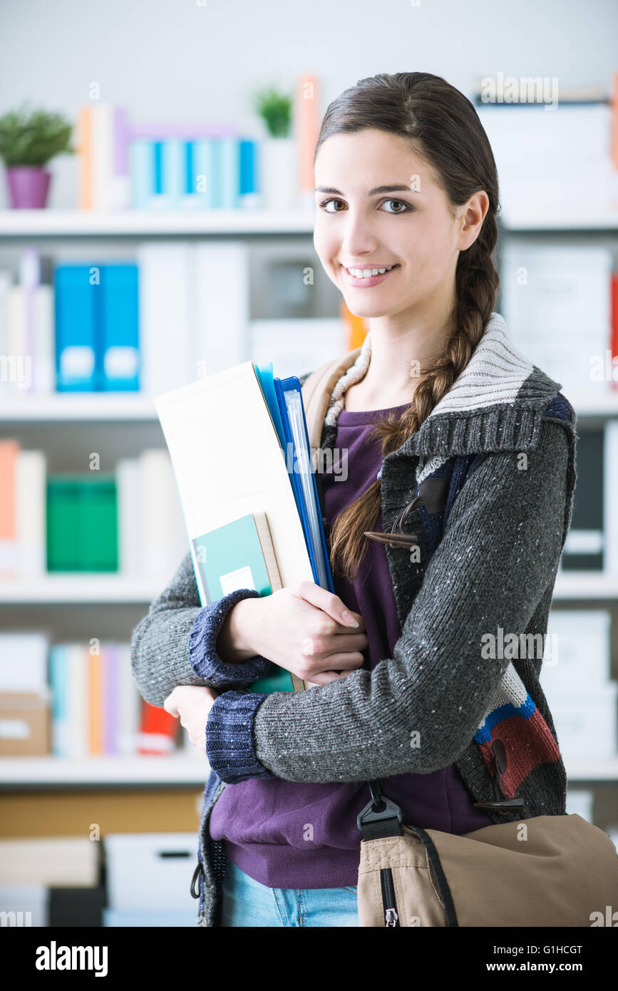 Confident smiling college student posing in the library, she is smiling at camera and holding notebooks - Stock Image
