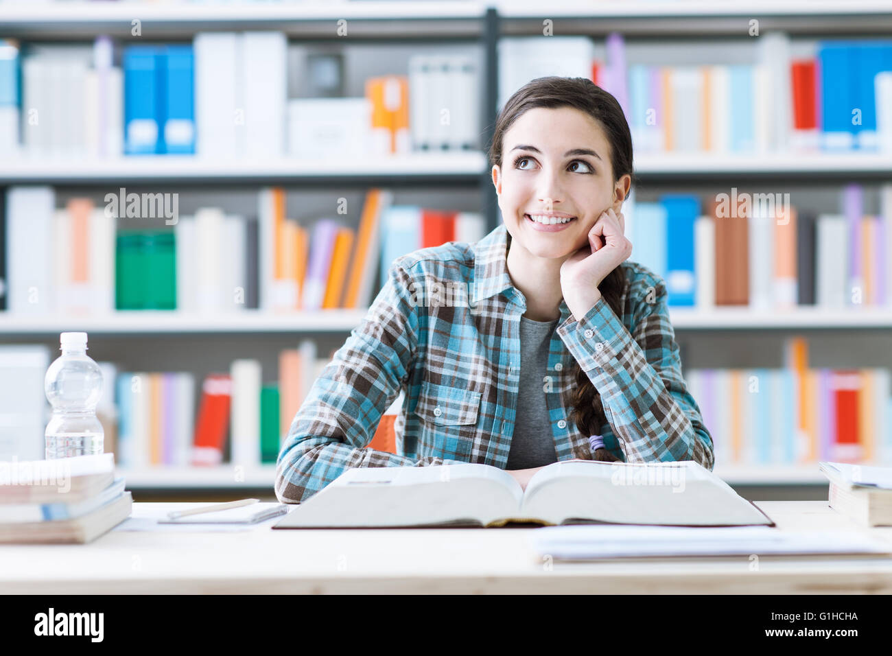 Smiling student girl in the library studying and day dreaming, she is thinking with hand on chin and looking up, - Stock Image