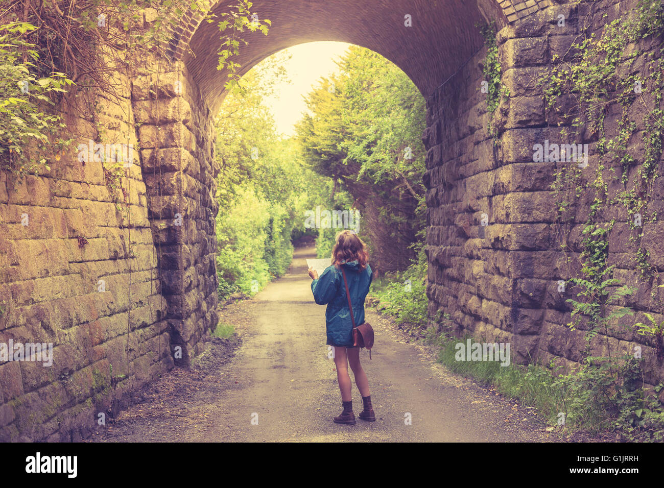 A young woman is lost in a forest below a railway bridge and is studying a map - Stock Image