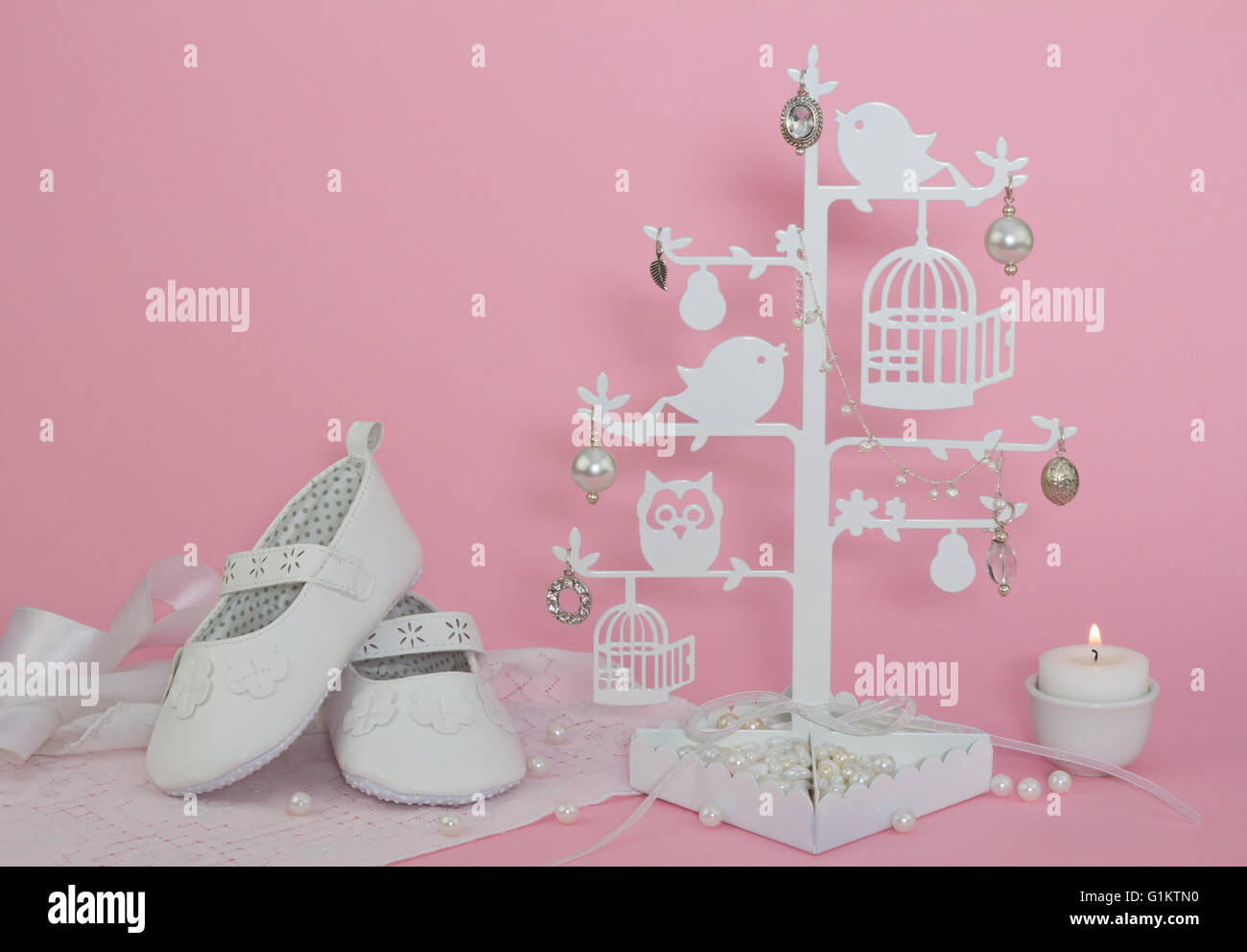 baby girl shoes candle and pearls pink invitation background stock
