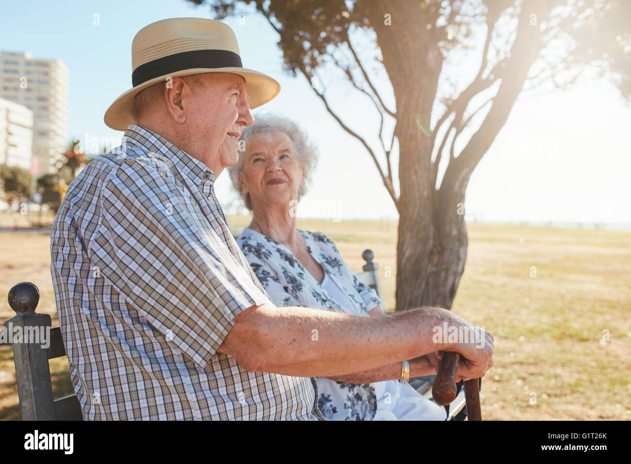 Side view shot of elderly man and woman sitting on a bench outdoors. Senior couple sitting on a park bench. - Stock Image