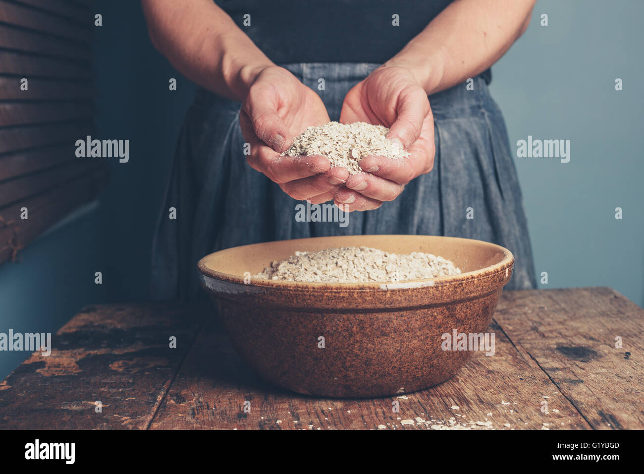 A young woman is standing with a handful of oats - Stock Image