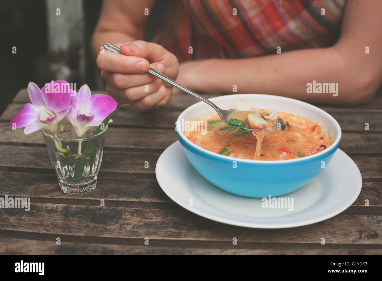 A young woman is eating tom yum soup at a table outside - Stock Image