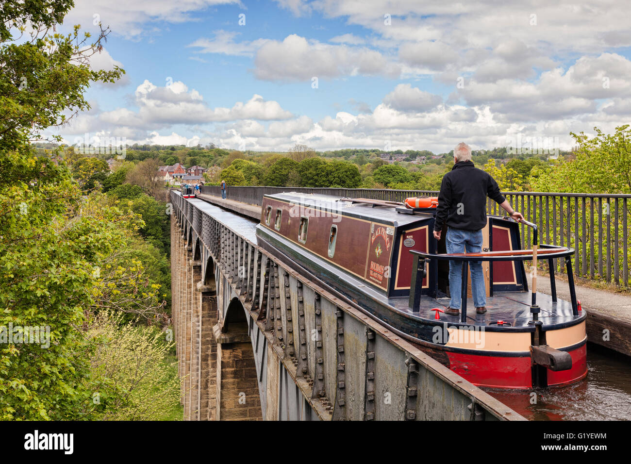 Man with his hand on the tiller, steering narrowboat over the Pontcysyllte Aqueduct, built by Thomas Telford, on Stock Photo
