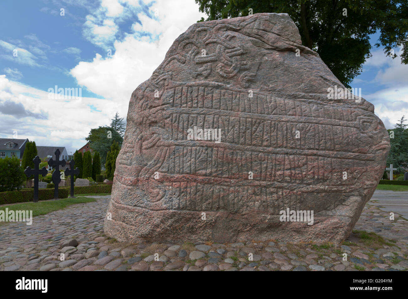 Runic inscription on the large Jelling rune stone from the tenth century raised by King Harald Bluetooth in Jelling. Stock Photo
