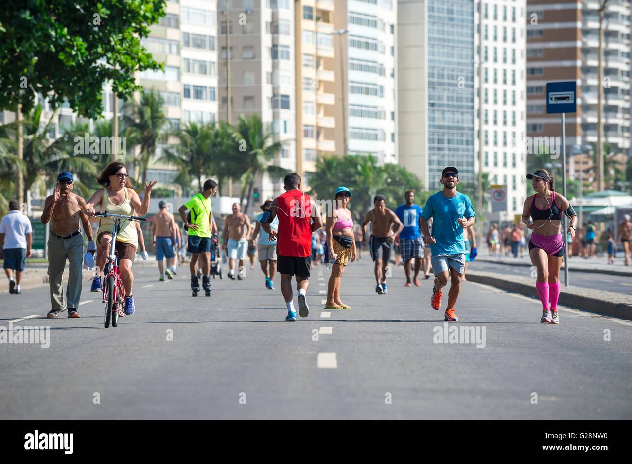 RIO DE JANEIRO - APRIL 3, 2016: Joggers and walkers share the beachfront Avenida Atlântica on a car-free morning - Stock Image
