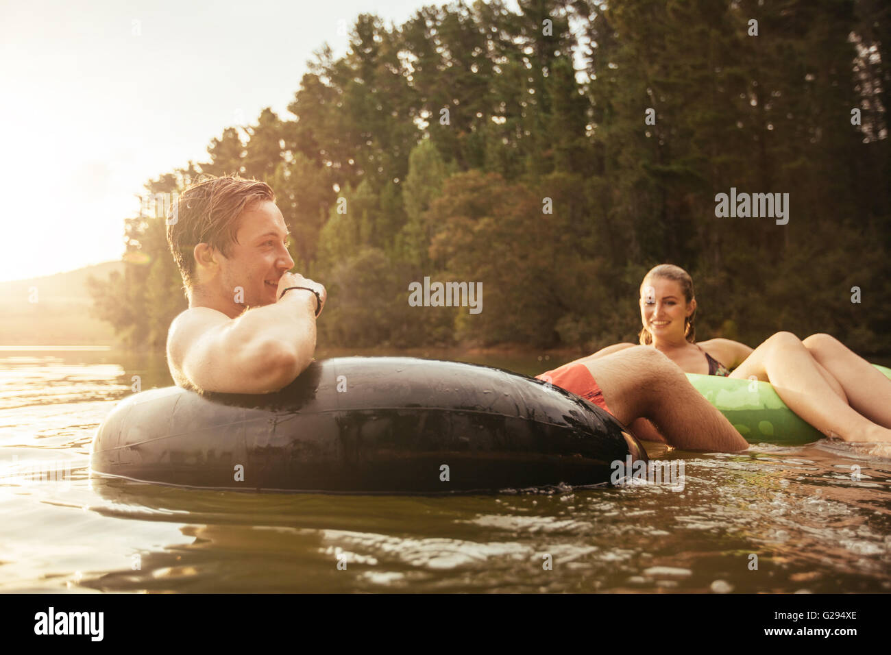 Portrait of happy young man in lake on inflatable ring with his girlfriend. Young couple relaxing in water on a - Stock Image