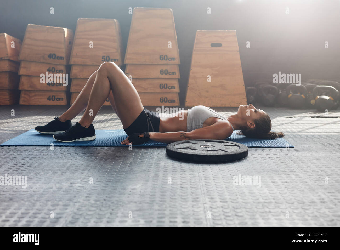 Side view shot of fitness woman resting on exercise mat with a heavy weight plate on floor. Female athlete lying - Stock Image