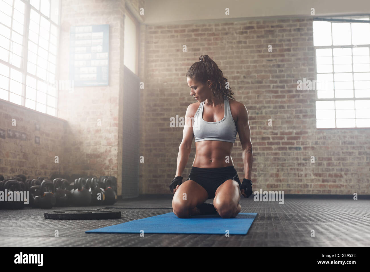 Indoor shot of  fitness young woman sitting on yoga mat at gym. Muscular young female athlete taking a break from - Stock Image
