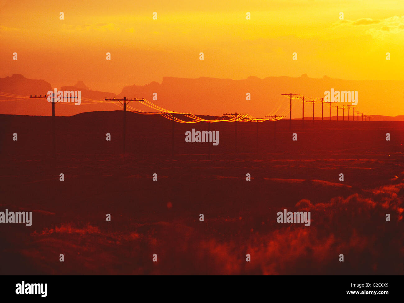 TELEPHONE & ELECTRIC POWER LINES AT SUNSET IN SOUTHERN UTAH; USA - Stock Image