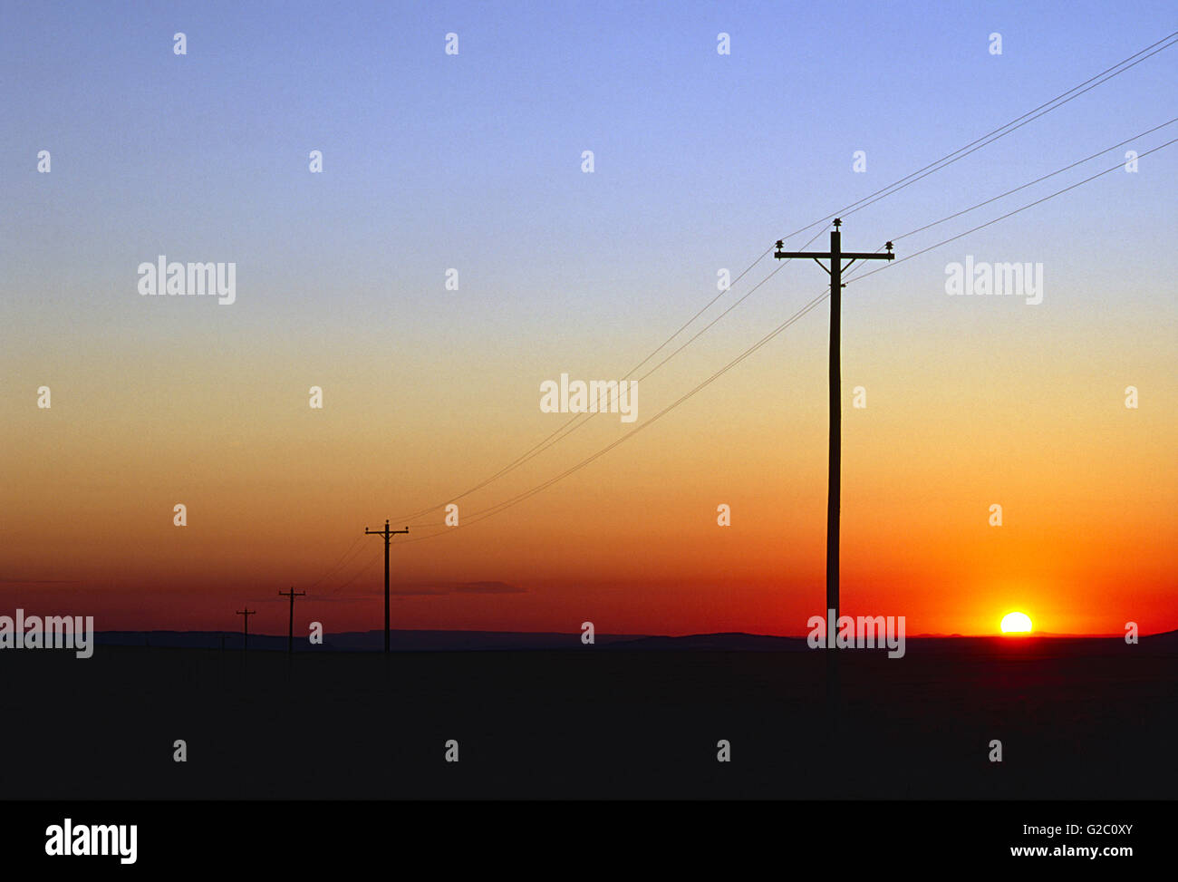 TELEPHONE & ELECTRIC POWER LINES AT SUNSET; NEAR SHIPROCK; NEW MEXICO; USA - Stock Image