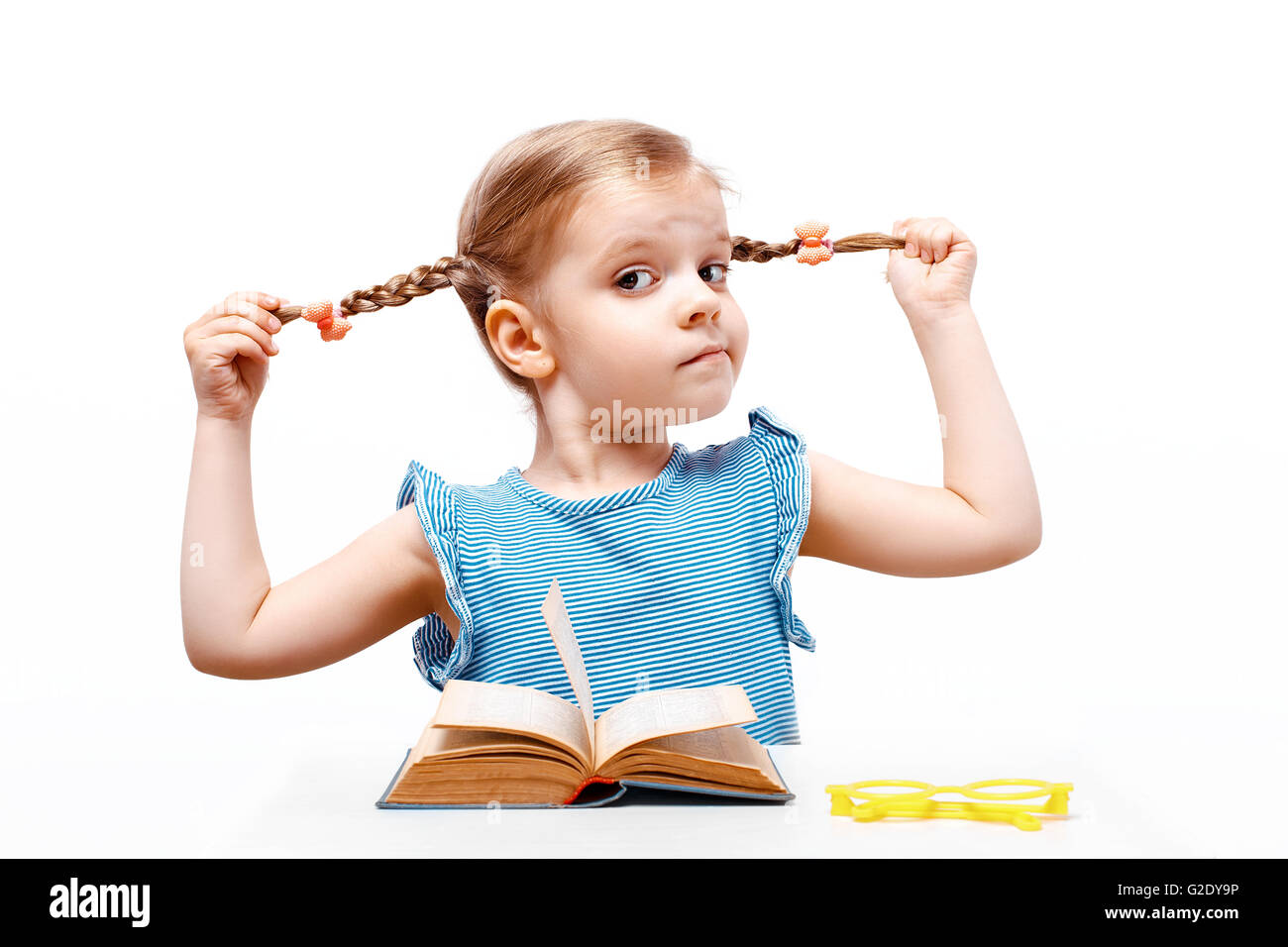 Little girl holds with hands the braids so far sits at a table. white background. isolate. - Stock Image