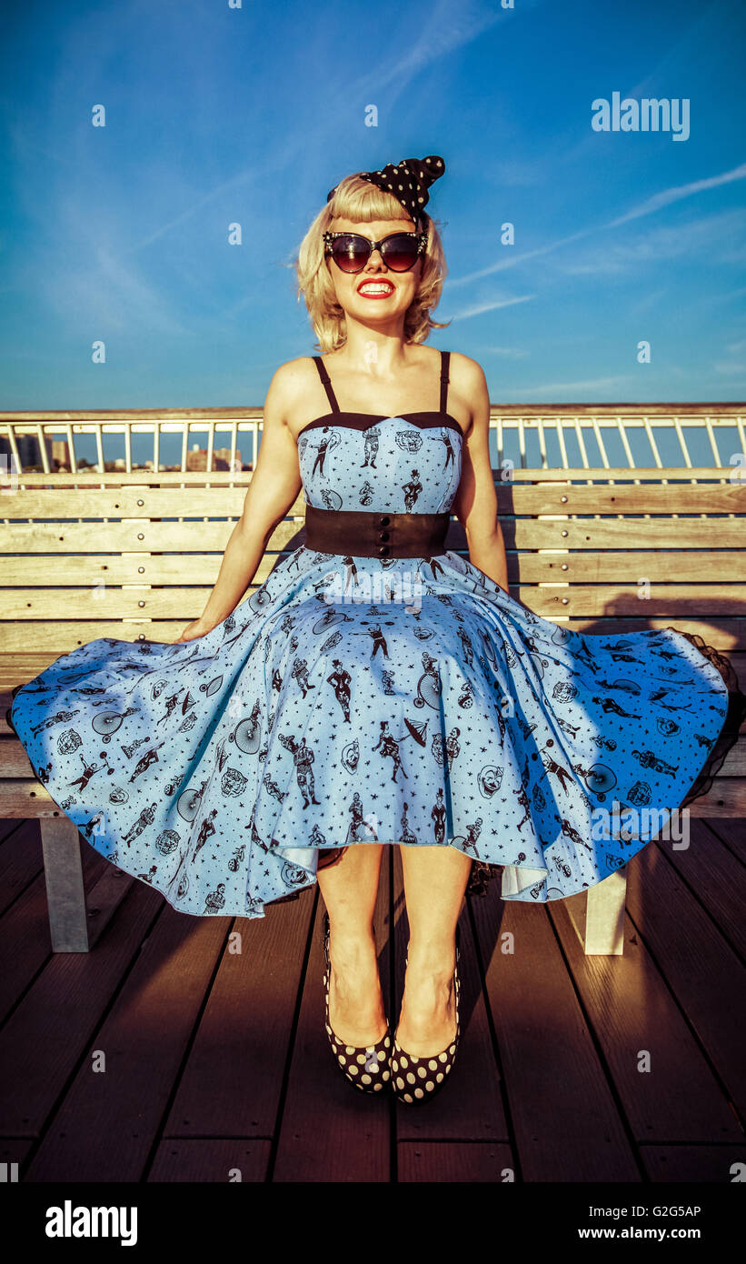 Young Adult Woman in Retro Dress and High Heels Sitting on Boardwalk Bench at Beach - Stock Image