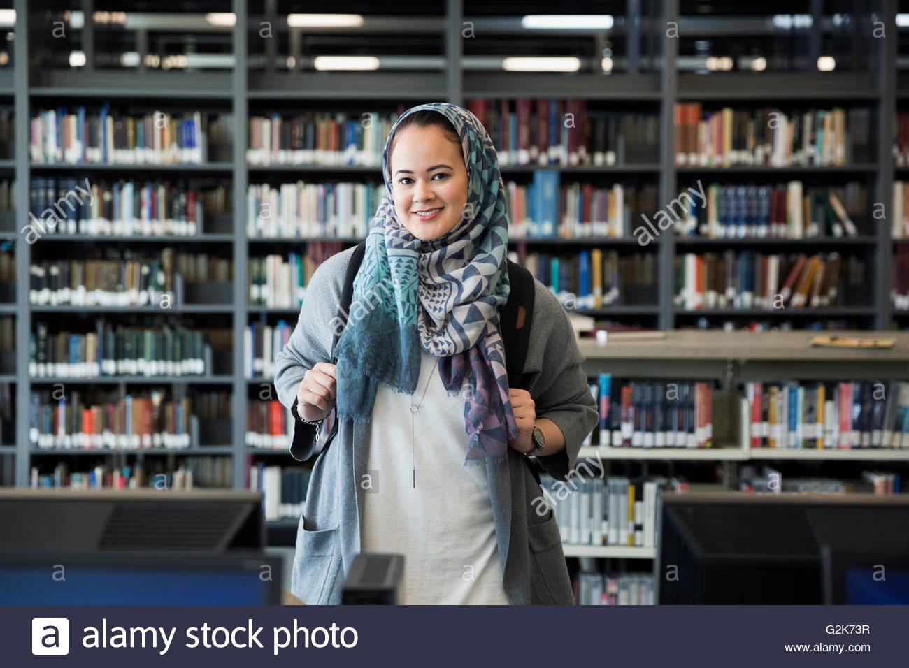 Portrait smiling college student wearing hijab in library - Stock Image