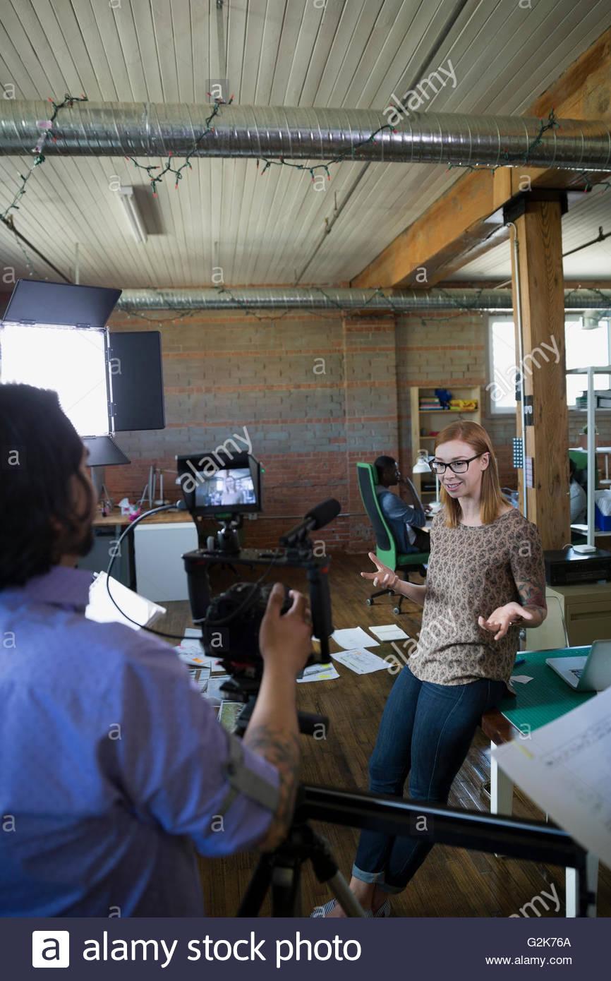 Cameraman filming creative businesswoman for tutorial - Stock Image