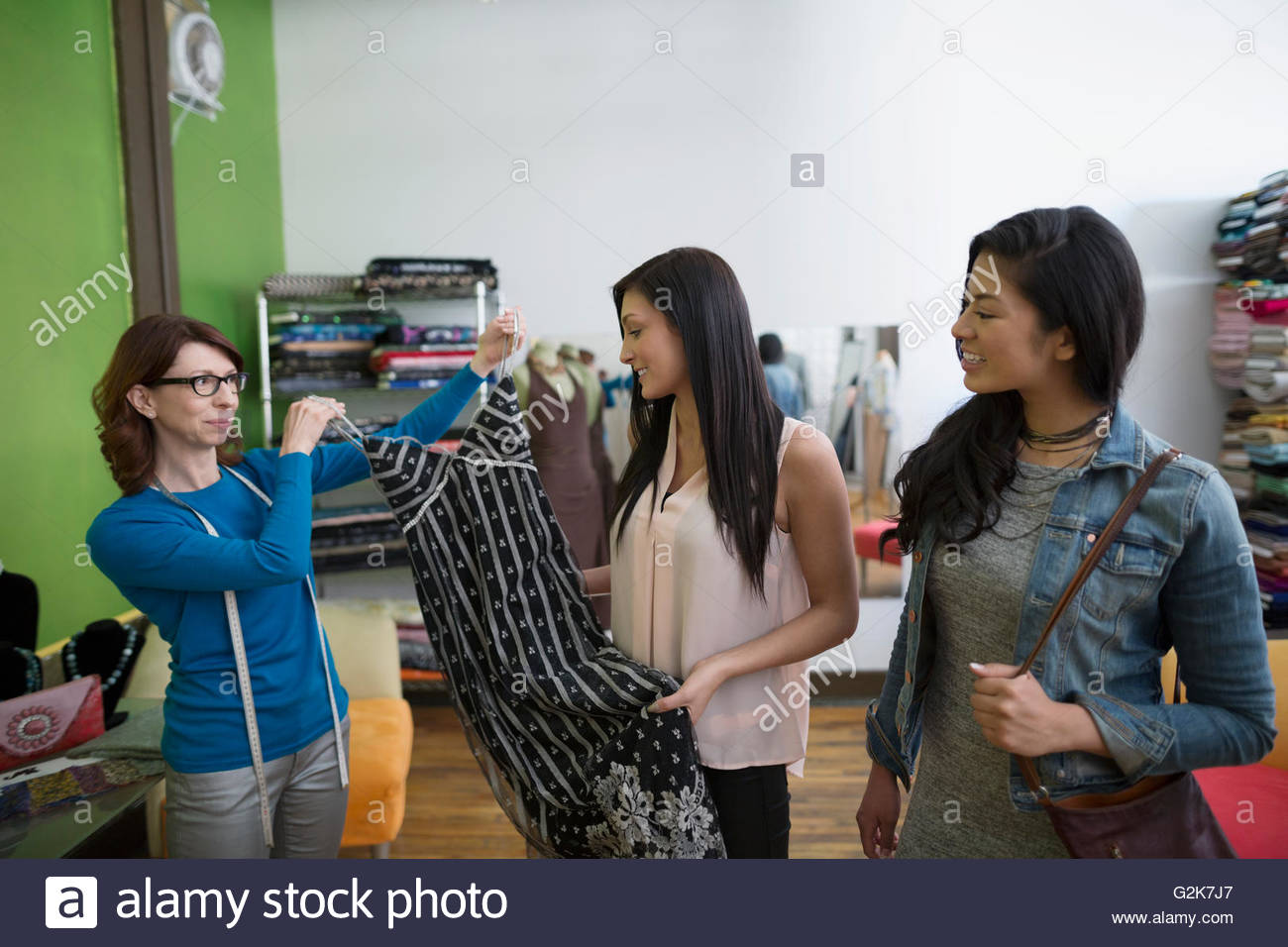Dressmaker showing women dress - Stock Image