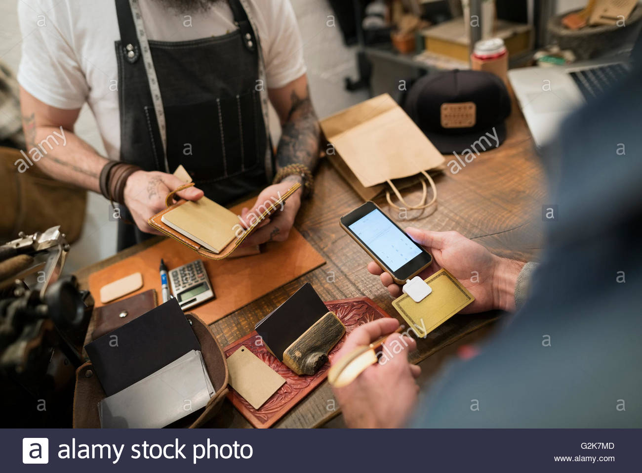 Customer using credit card reader in leather shop - Stock Image