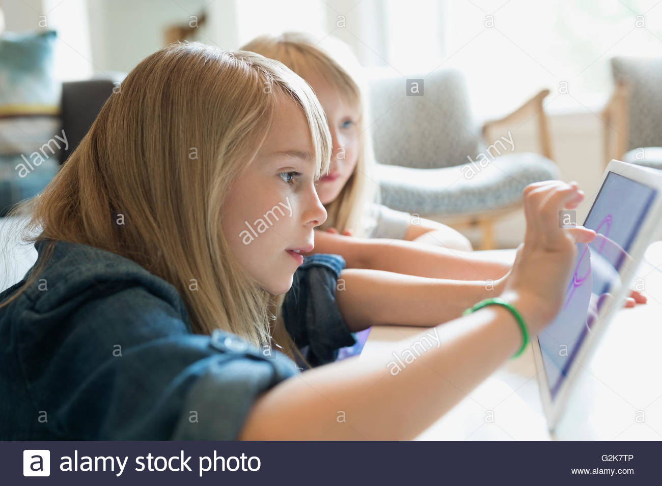 Sisters drawing with digital tablet in living room - Stock Image