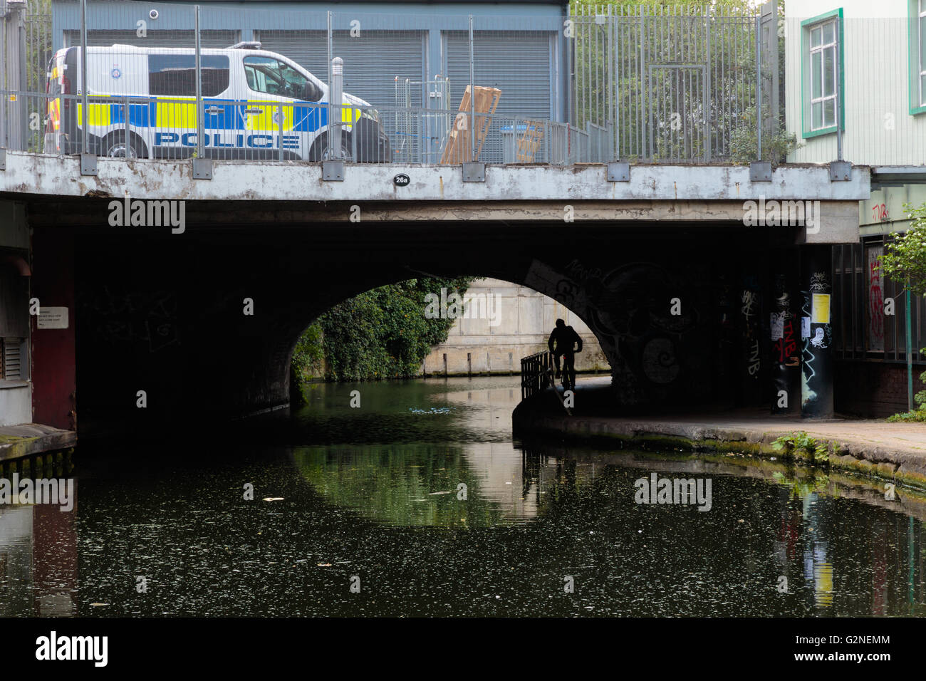 Street security metaphor: UK police vehicle and an unidentified cyclist passing under the bridge on the canal bank - Stock Image