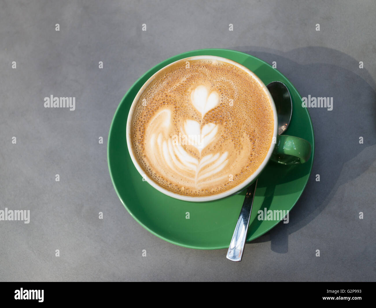 Cup, saucer and spoon, latte coffee with heart pattern on surface Stock Photo