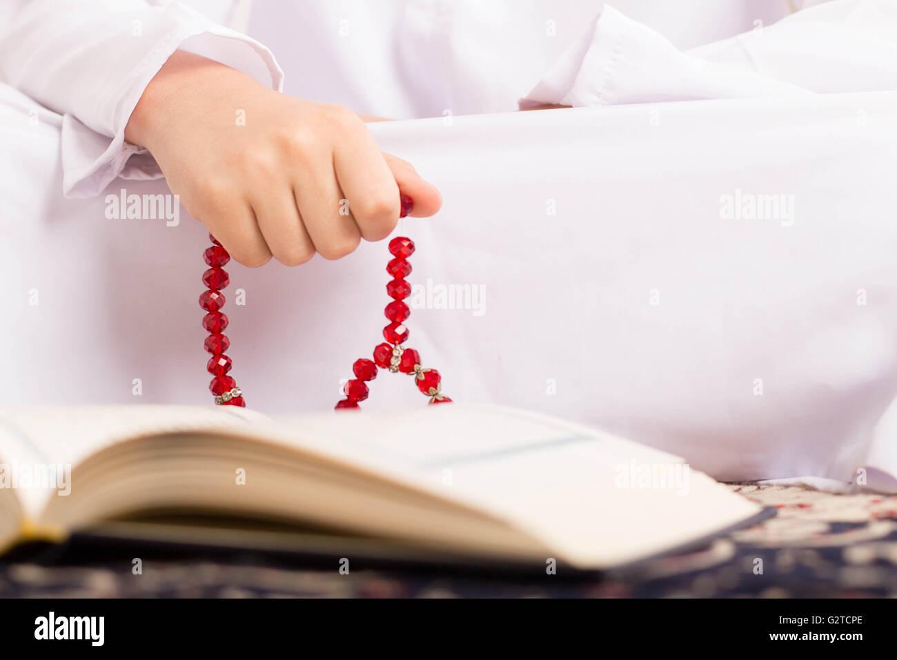 Muslim kid reading Quraan in Ramadan - Stock Image