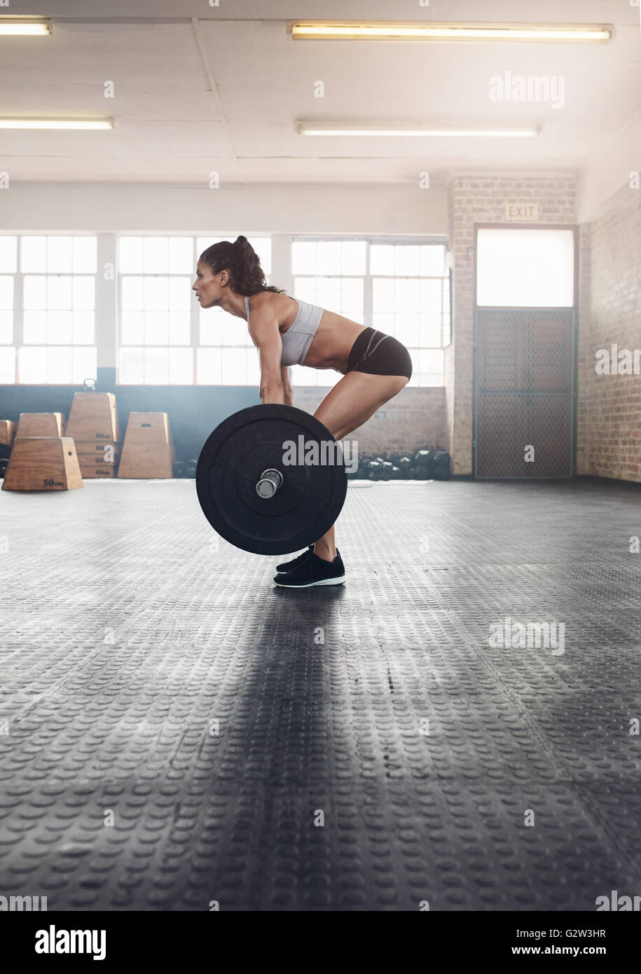 Side view of fitness woman doing exercise with a heavy weights  in gym. Muscular woman practicing weightlifting - Stock Image