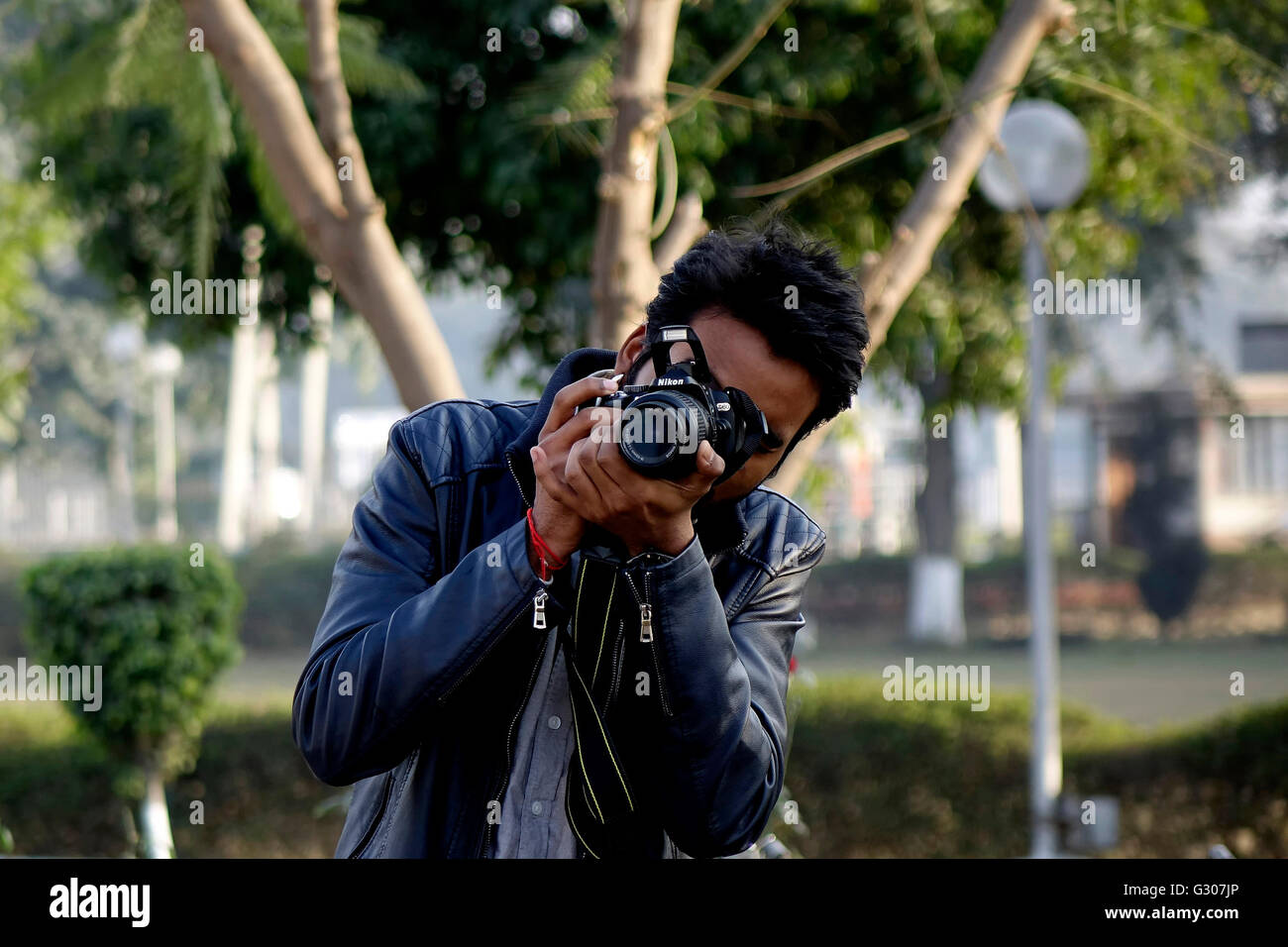 A young photographer clicking his subject using a DSLR - Stock Image