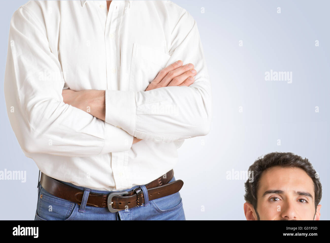 Height difference between two men in a blue background - Stock Image