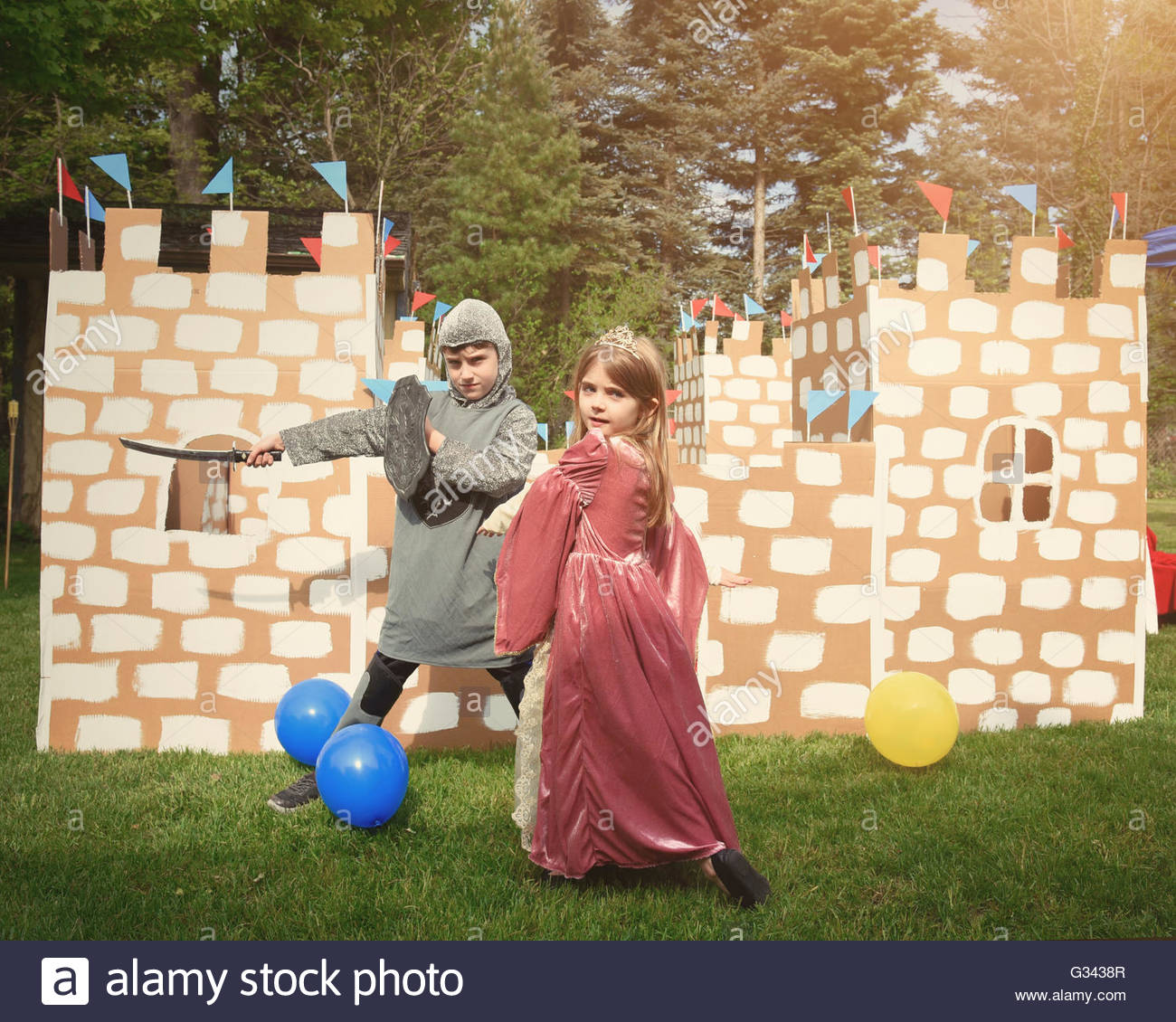 Children are dressed in a knight and princess costume in front of a homemade cardboard castle outside for a creative - Stock Image