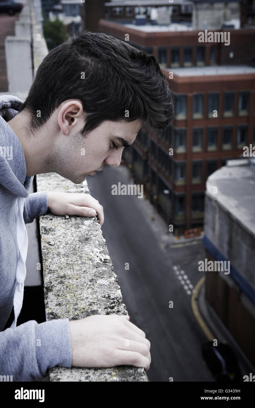 Depressed Young Man Contemplating Suicide On Top Of Tall Building - Stock Image