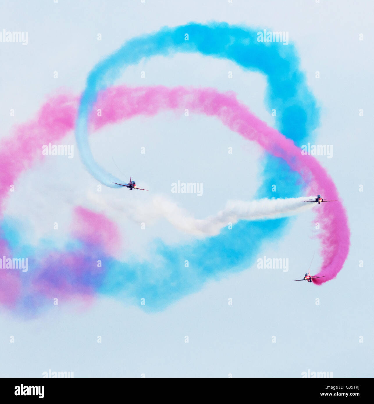 Three of the Red Arrows flying towards the camera in formation, with colourful smoke, Duxford Airshow, UK - Stock Image