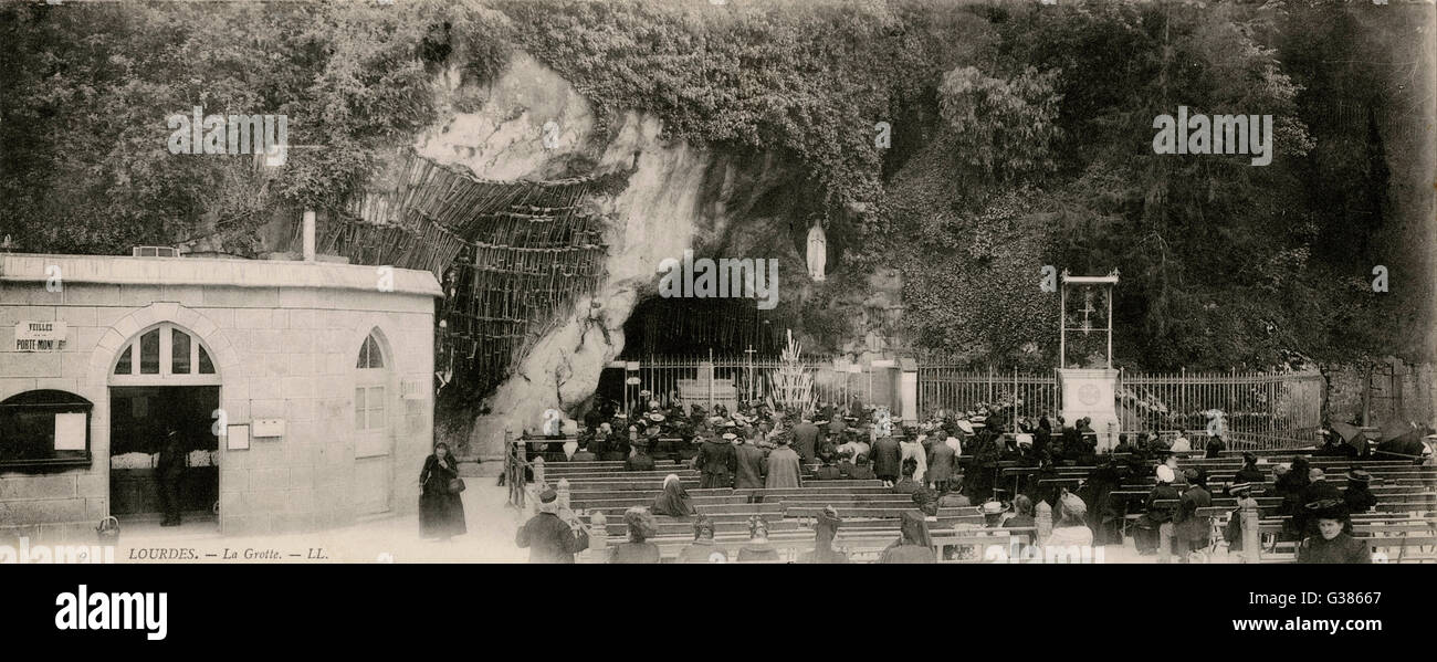 Pilgrims at the Grotto in Lourdes, France.  More benches have been added, and the quantity of discarded crutches - Stock Image