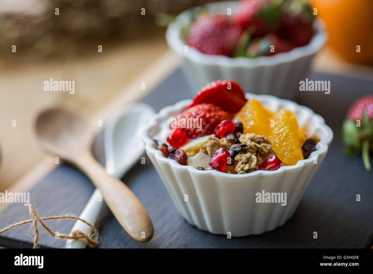 Granola with Orange, Strawberry, Cacao nibs and Pomegranate on yogurt - Stock Image