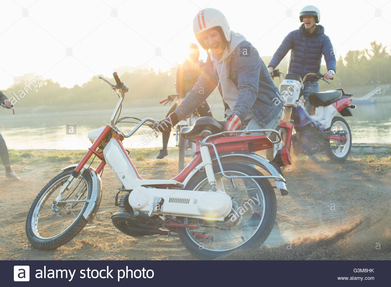 Small group of friends riding mopeds near lake - Stock Image
